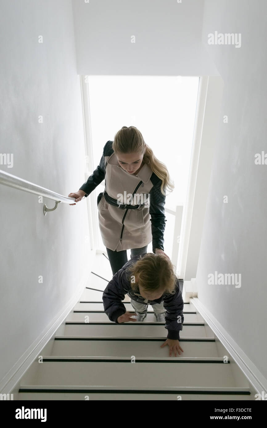 Mother and son (4-5) walking up stairs - Stock Image
