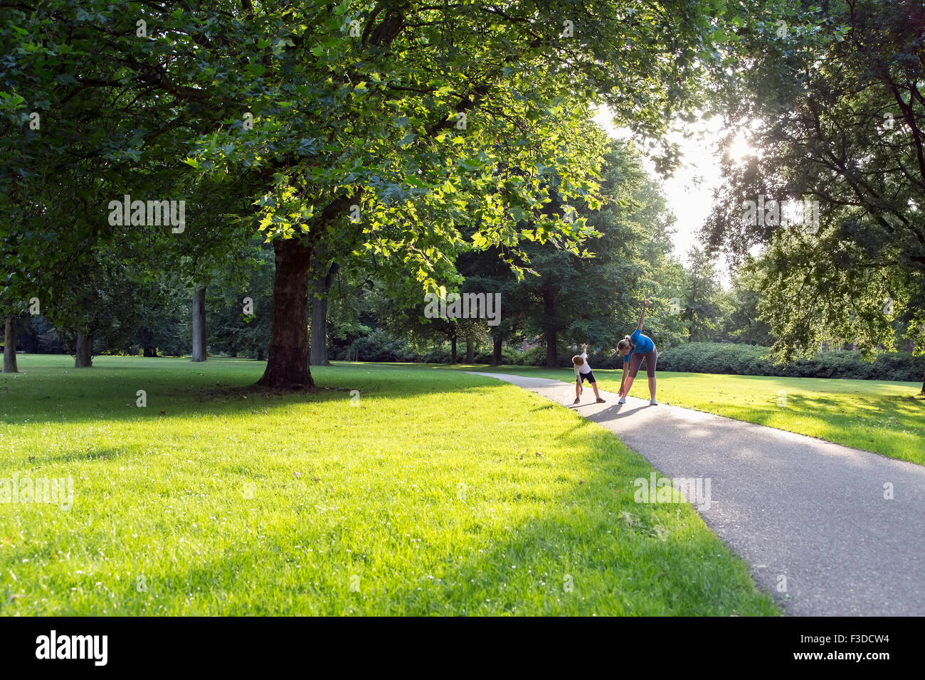 Mother and son (12-13) exercising in park - Stock Image