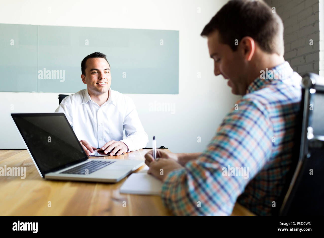 Man being interviewed in conference room - Stock Image