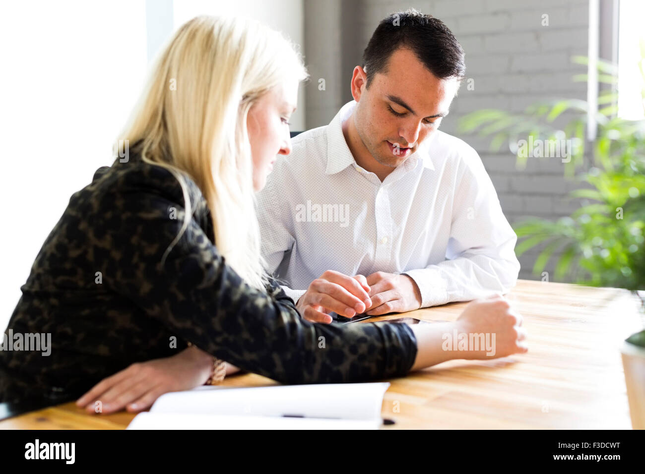 Woman discussing idea with man - Stock Image