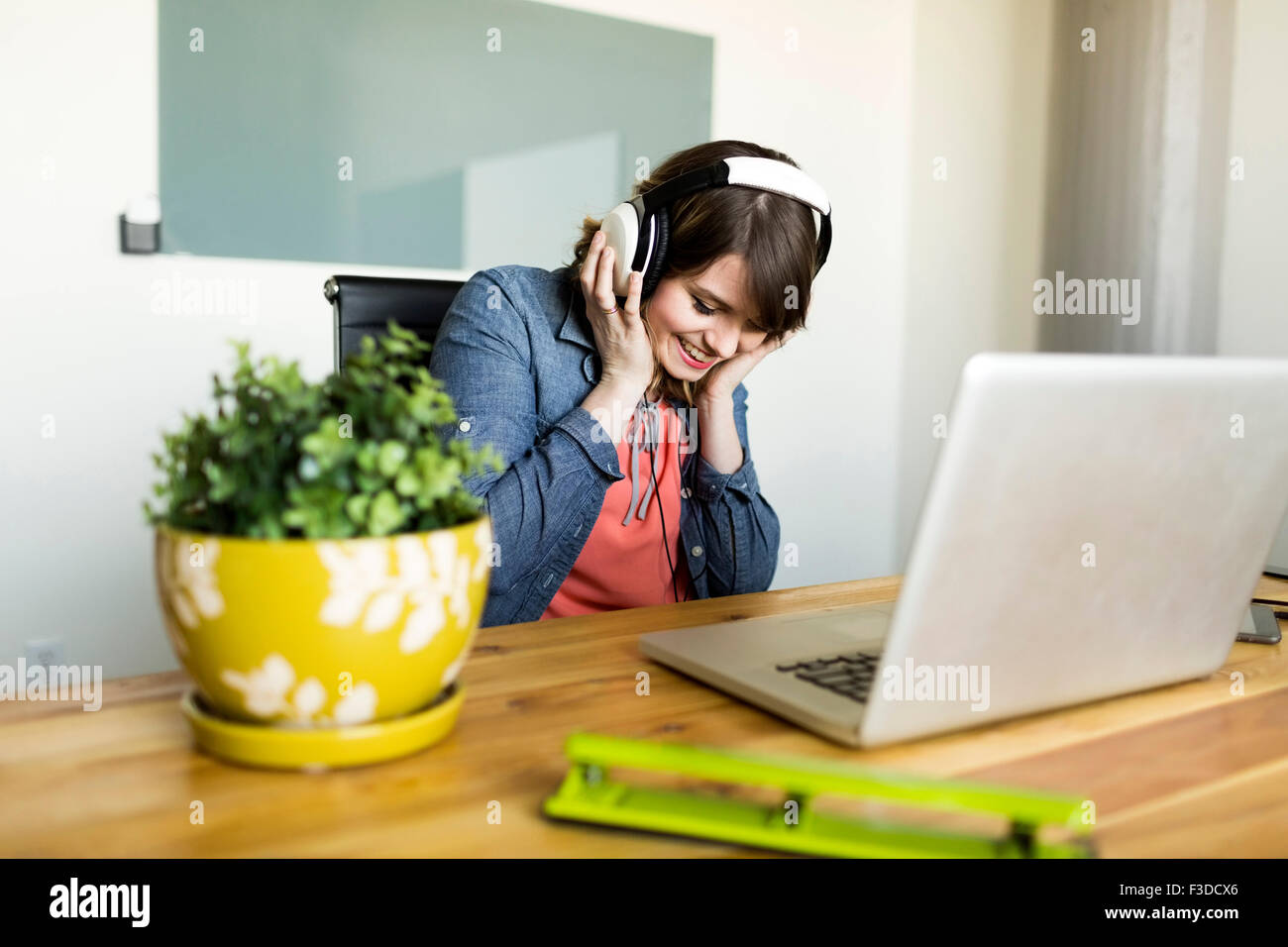 Young woman listening to music in office Stock Photo