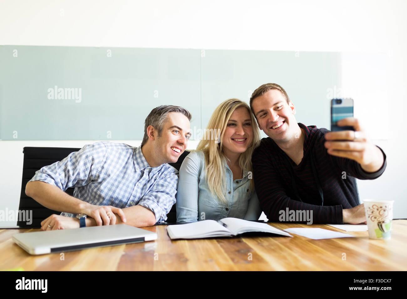 Office workers taking selfie - Stock Image
