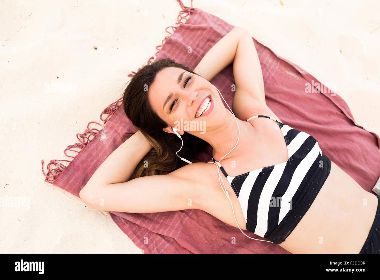 Woman in bikini relaxing on beach - Stock Image