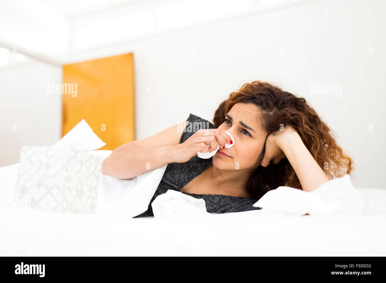 Woman blowing nose in bed - Stock Image