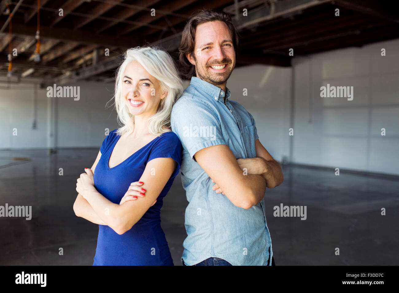 Woman and man standing in warehouse - Stock Image