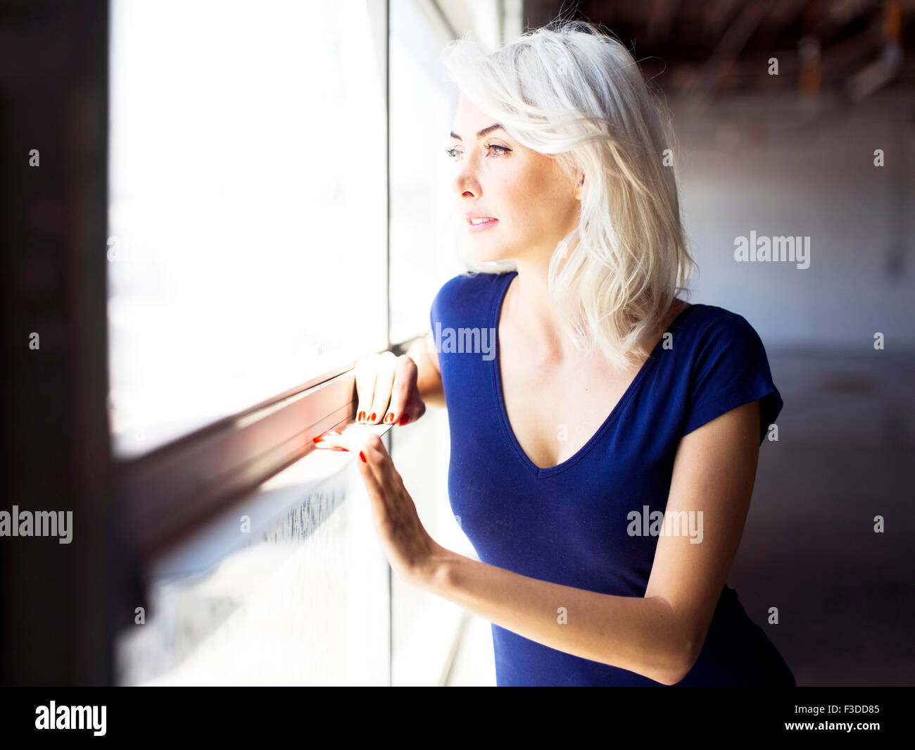 Woman looking through window Stock Photo