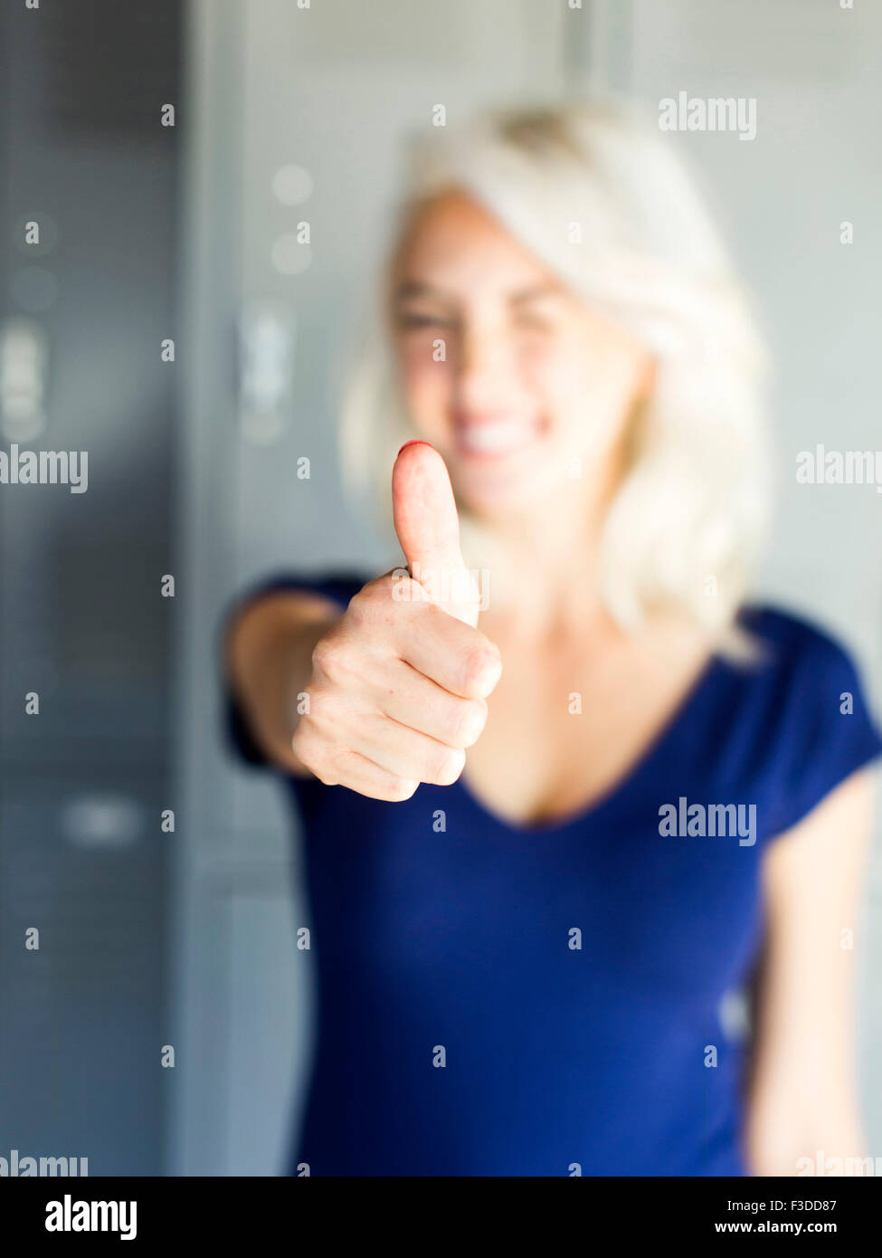 Woman holding thumb up - Stock Image