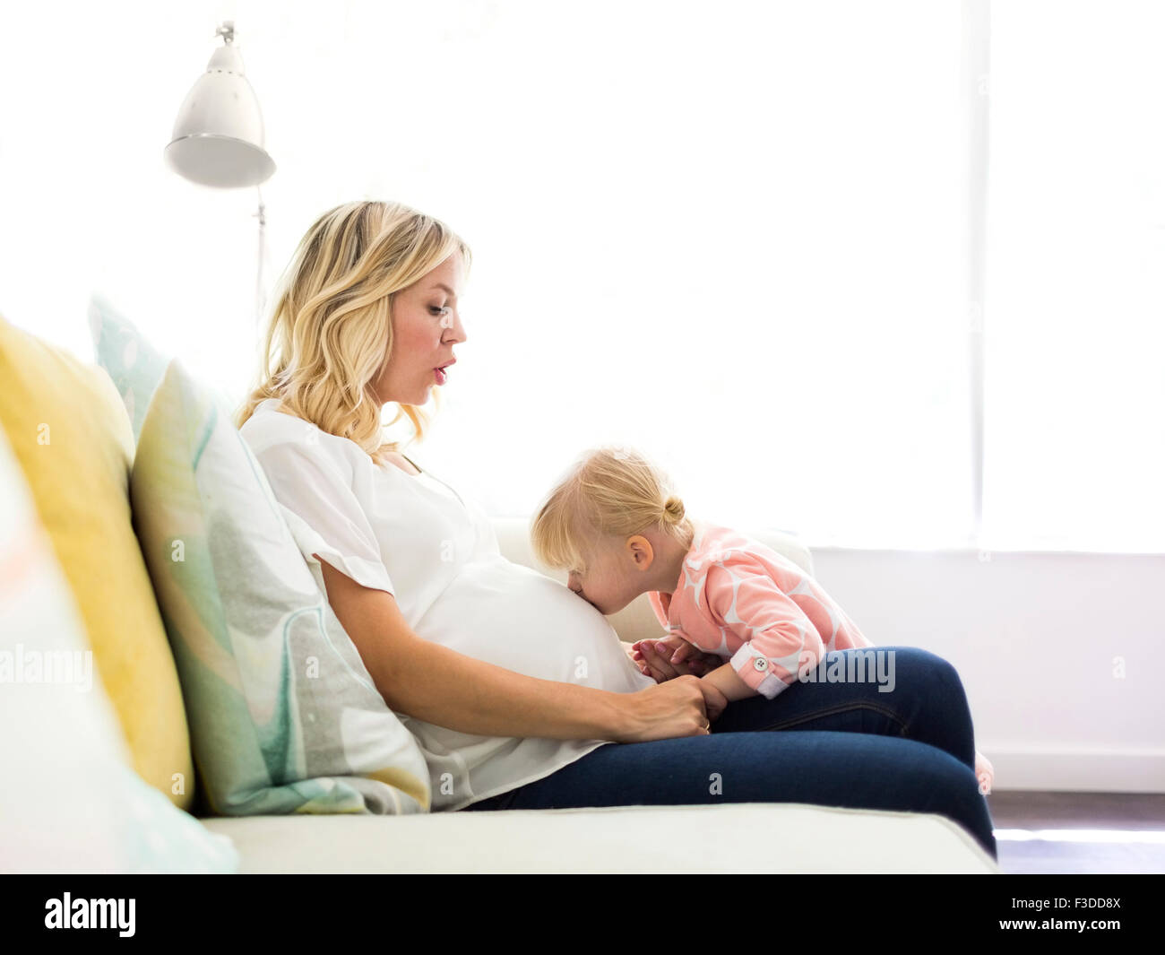Girl (2-3) kissing belly of mother - Stock Image