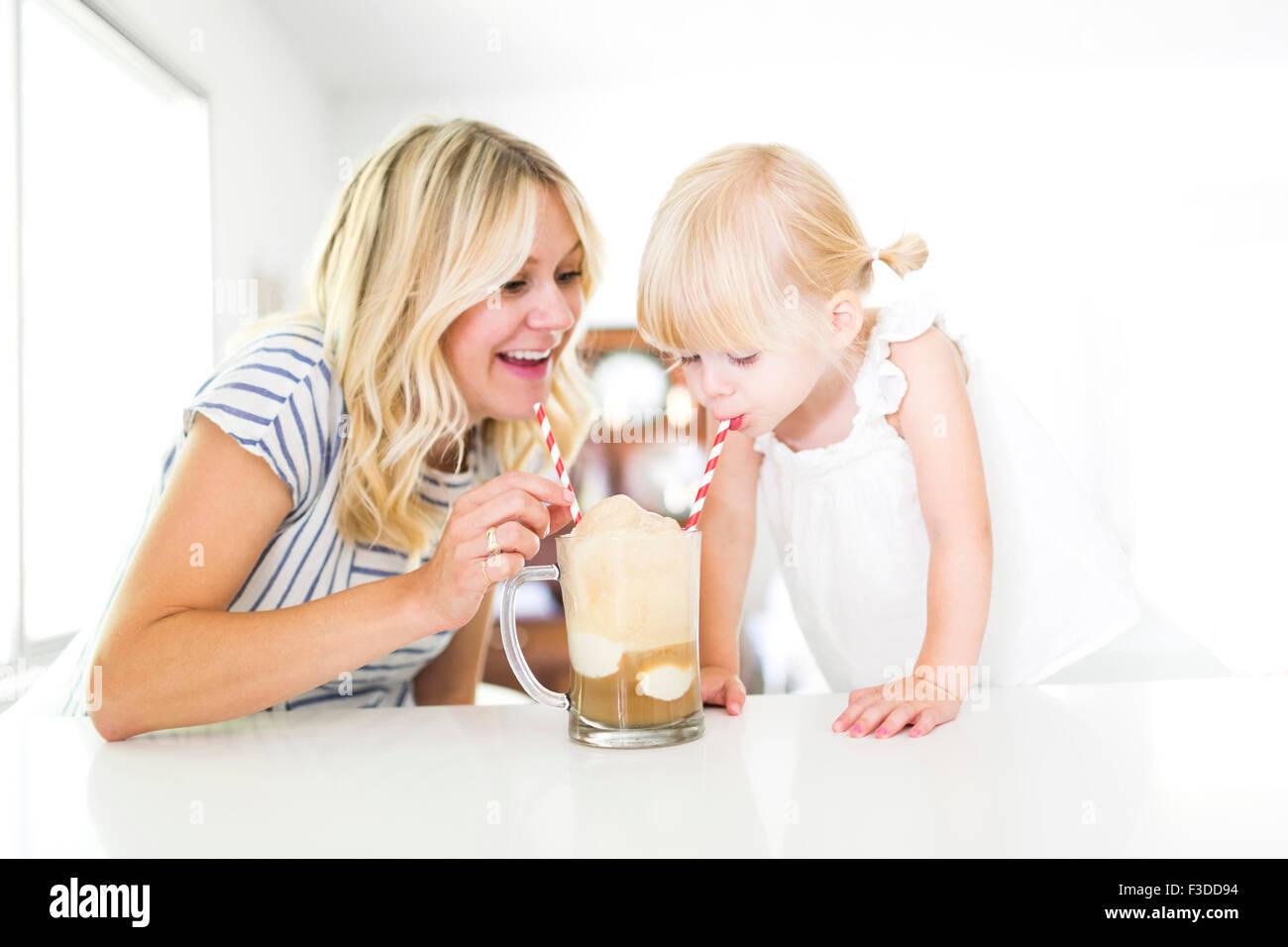 Mother drinking milkshake with daughter (2-3) - Stock Image