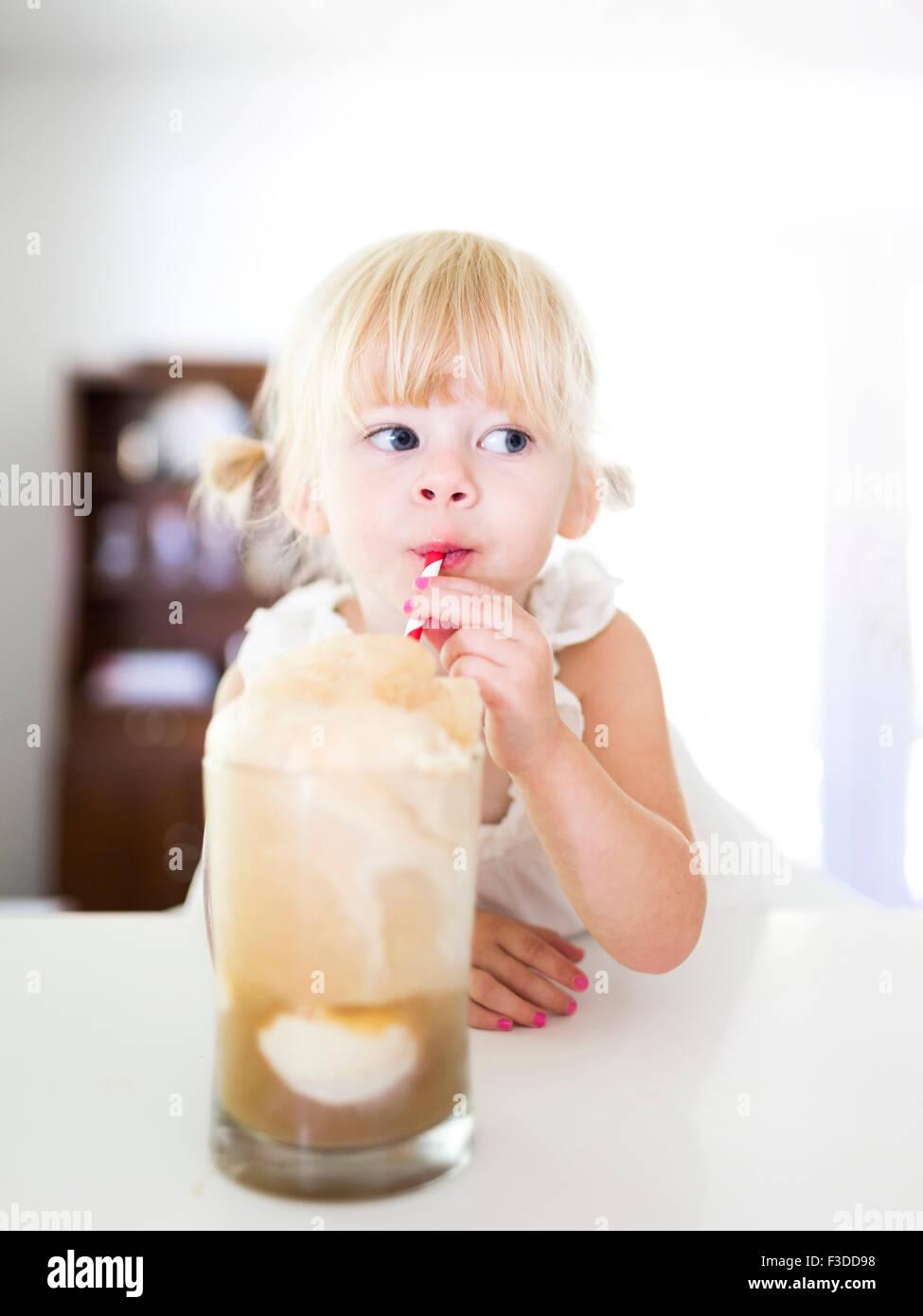 Girl (2-3) drinking milkshake - Stock Image