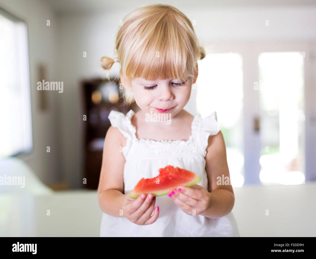 Portrait of girl (2-3) eating watermelon - Stock Image