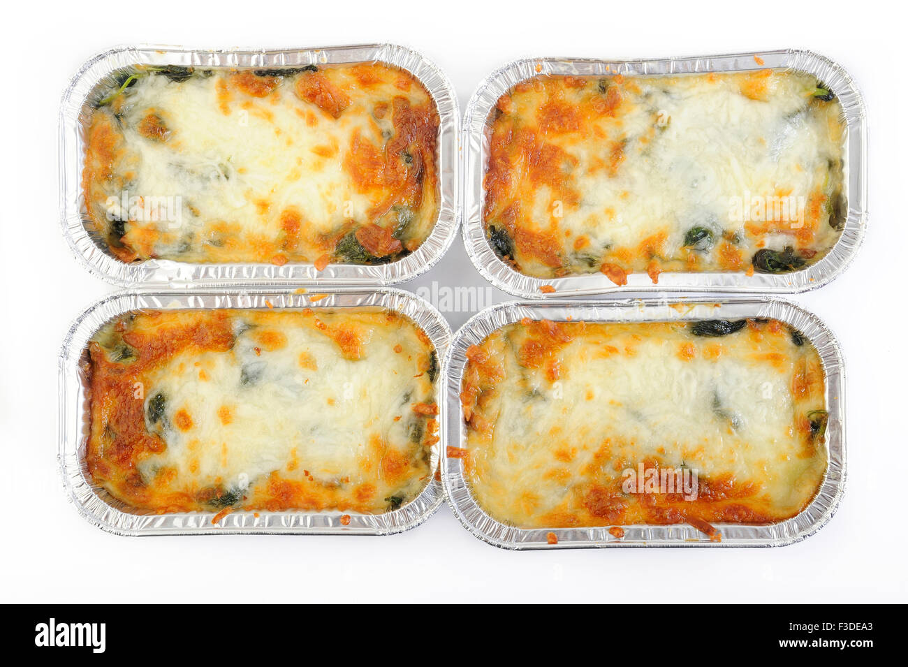 baked spinach with cheese in aluminium foil tray - Stock Image