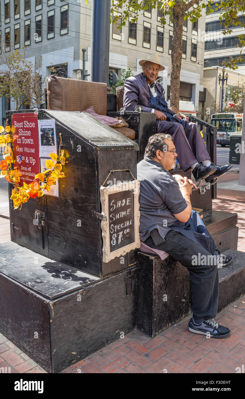 Two older men sit at an outdoor shoe shine stand on a sidewalk in downtown San Francisco, California. - Stock Image