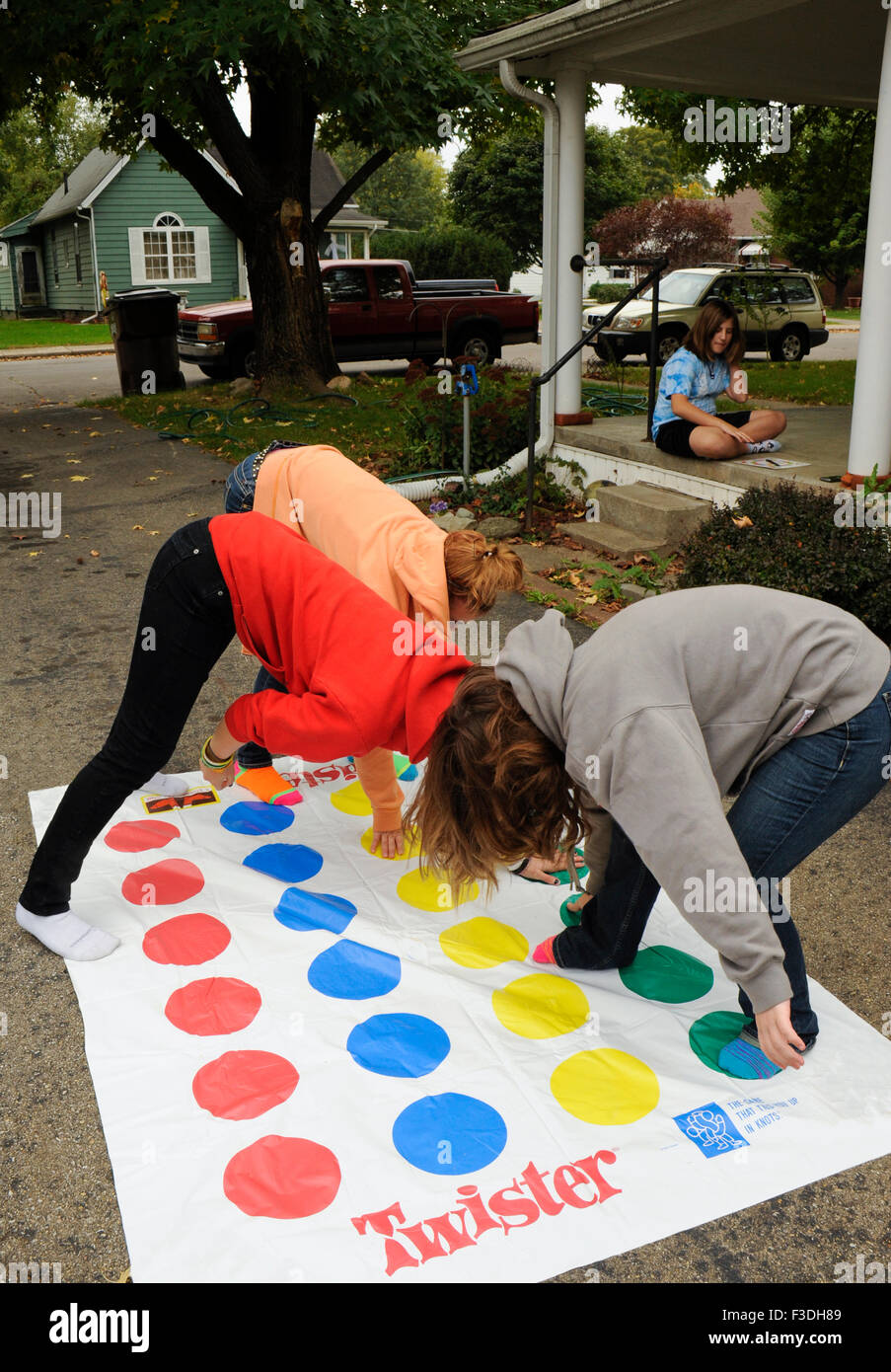 Teen and pre-teen girls playing Twister floor game. Stock Photo