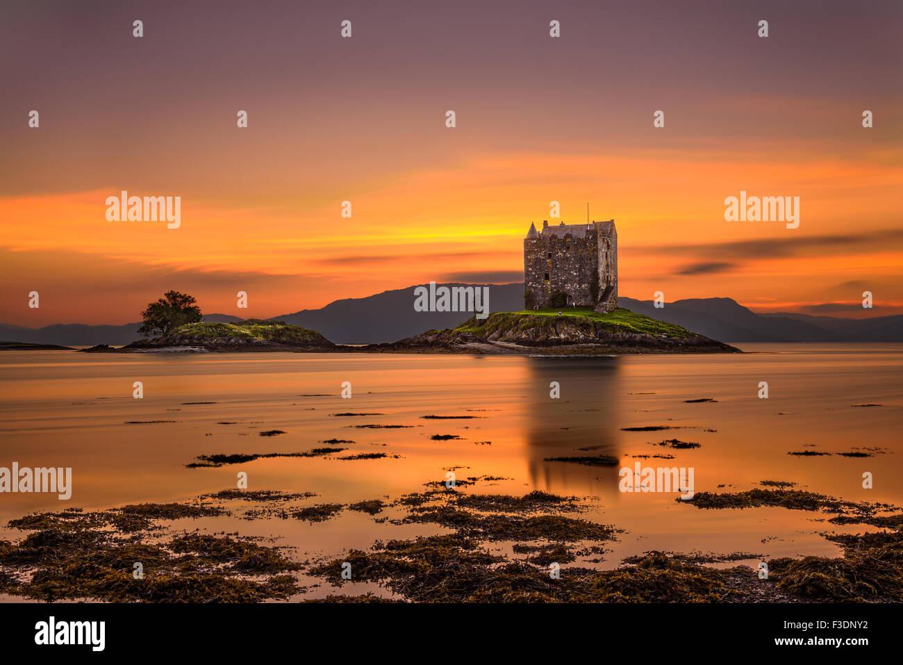 Sunset over Castle Stalker, Highlands, Scotland, United Kingdom. Long exposure and hdr processed. - Stock Image