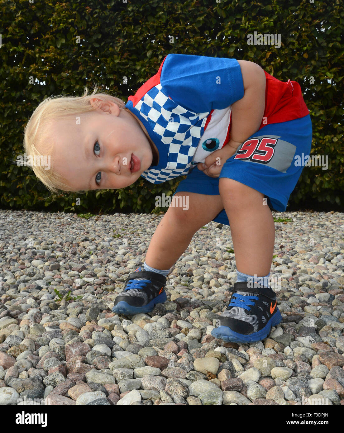 Little blond boy in colorful outfit, two and one-half years old, crouching and discovering his surroundings, Ystad, - Stock Image