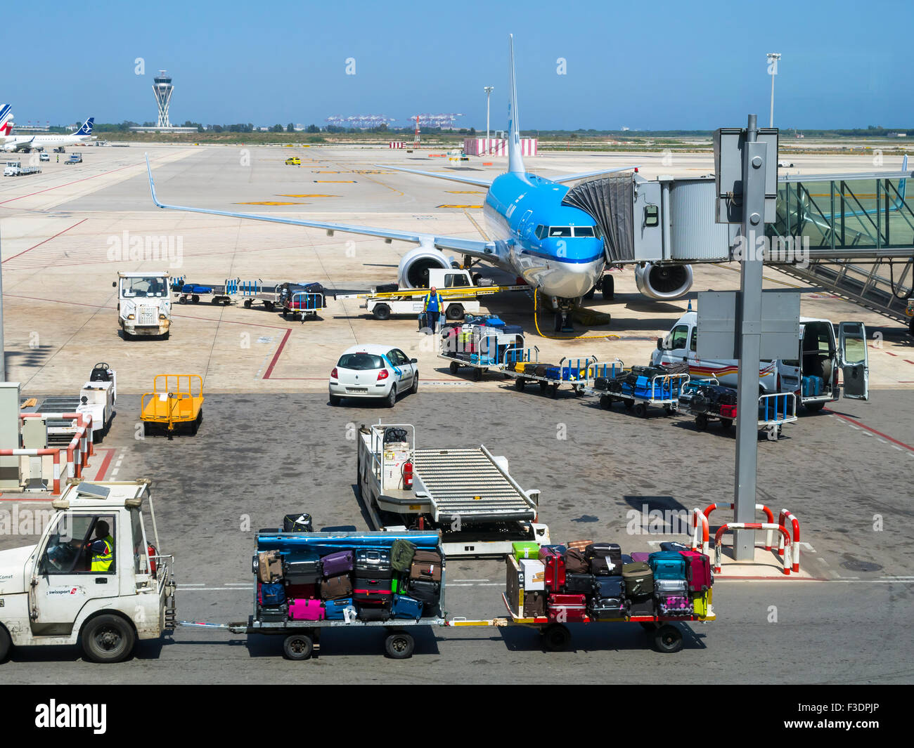 KLM aircraft at the terminal with luggage trollies, Barcelona airport, Spain - Stock Image