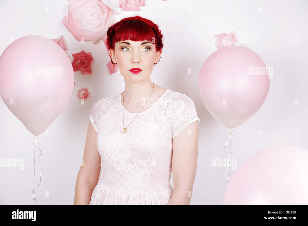 Beautifully romantic red haired girl in a contemporary studio setting - Stock Image