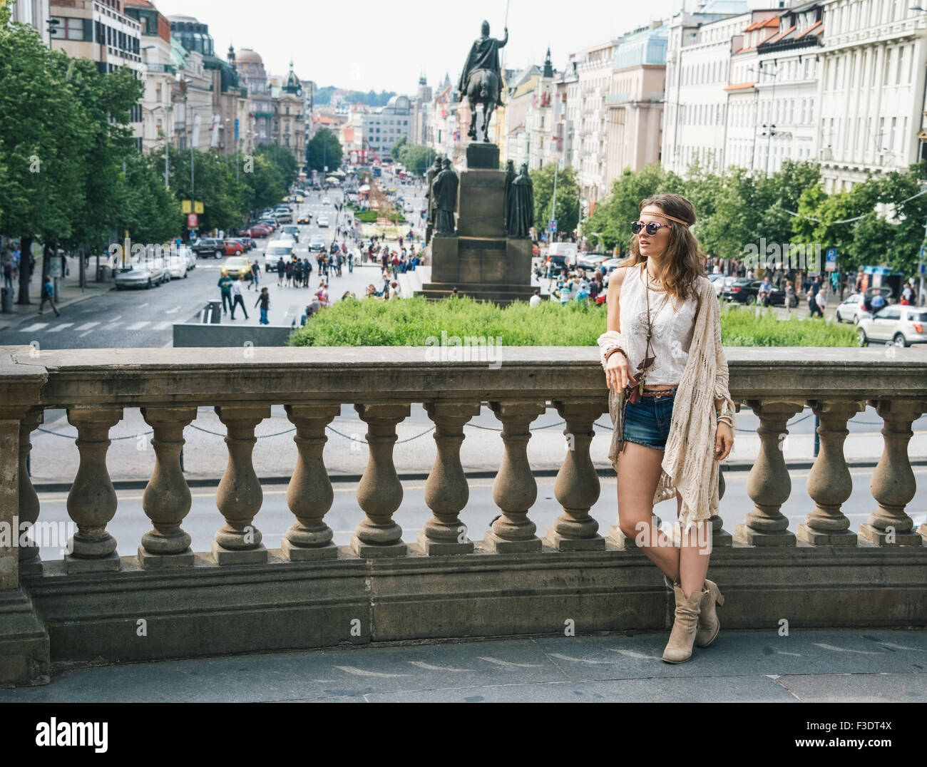 Trendy hippie woman tourist in jeans shorts, knitted shawl and white blouse standing on Wenceslas Square in Prague. - Stock Image