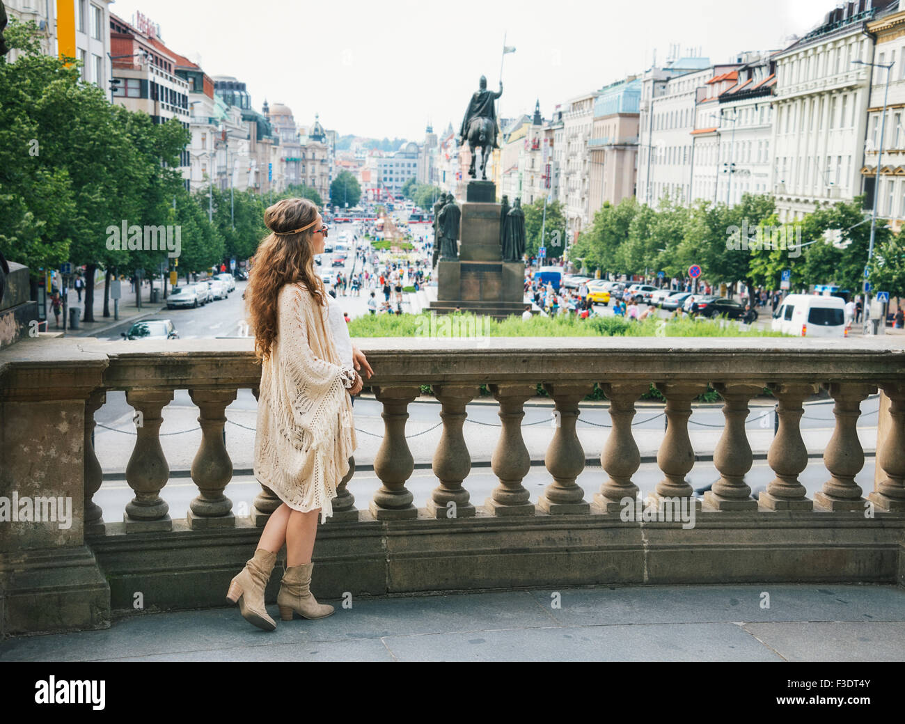 Longhaired bohemian woman tourist in knitted shawl standing on Wenceslas Squarein in Prague. In the background Saint - Stock Image