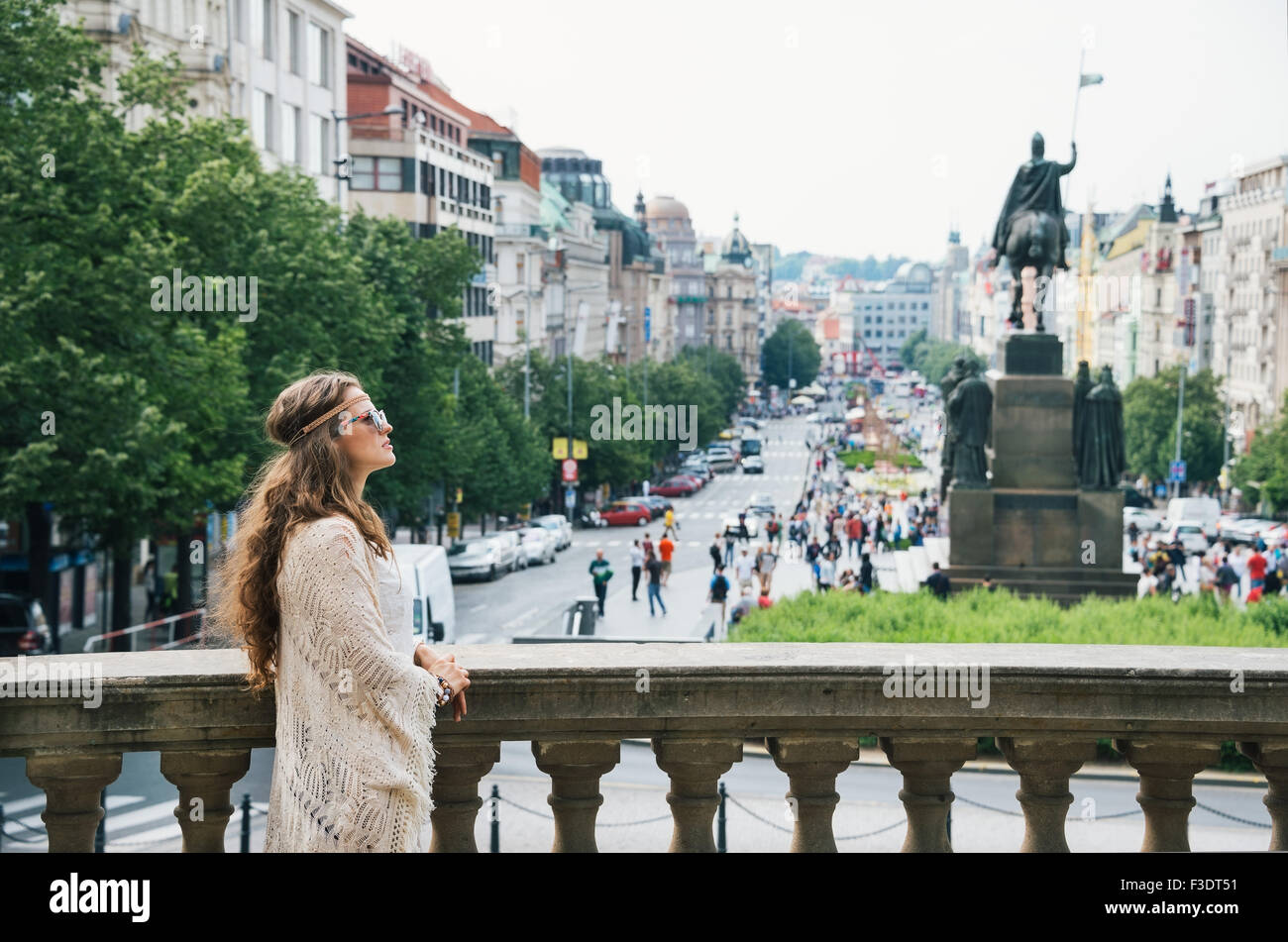Longhaired bohemian woman tourist sightseeing on Wenceslas Square in Prague. In the background Saint Wenceslas statue - Stock Image