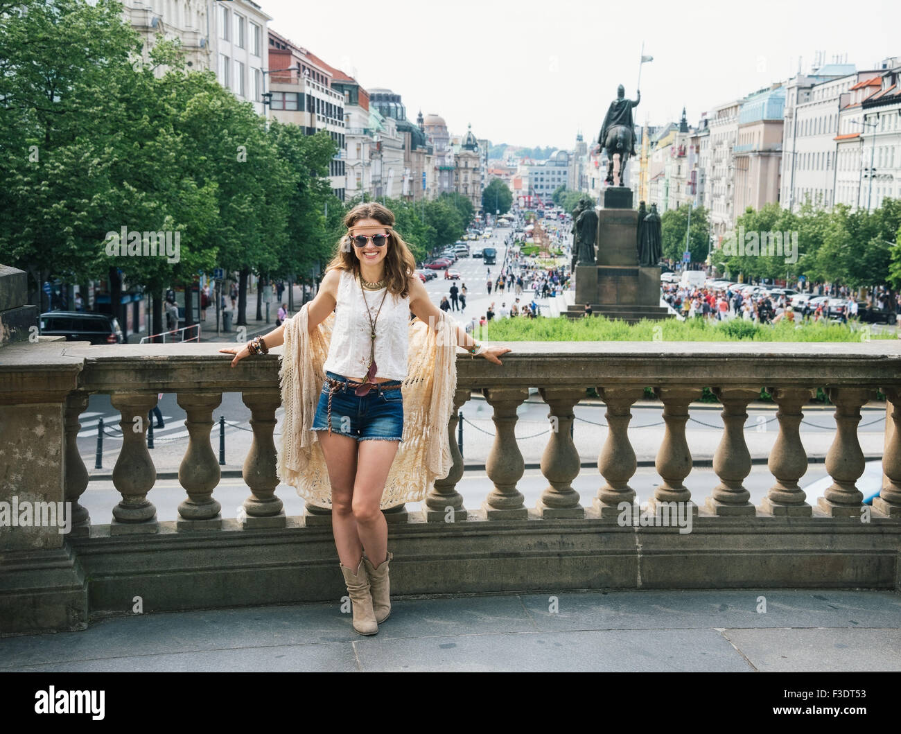 Full length portrait of cheerful longhaired hippy-looking woman tourist in knitted shawl and white blouse standing - Stock Image