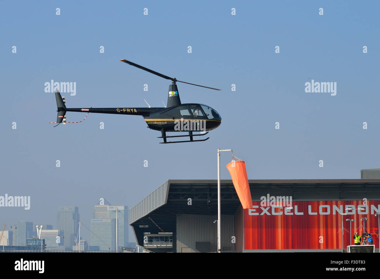 Robinson R44 G-FRYA operated by A2B Aero Limited comes in to land at London's Excel exhibition centre to participate - Stock Image