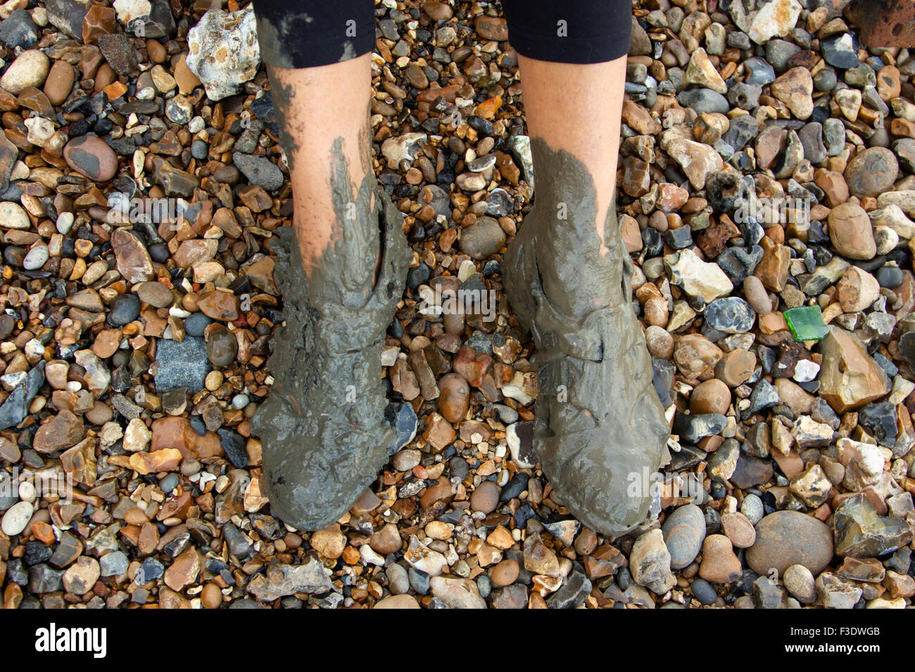 Woman with very muddy shoes. - Stock Image