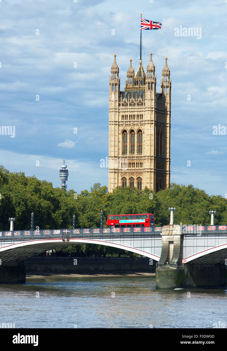 Red Bus crossing Lambeth Bridge in front of the Houses of Parliament and the BT Telecommunications Tower, London, - Stock Image