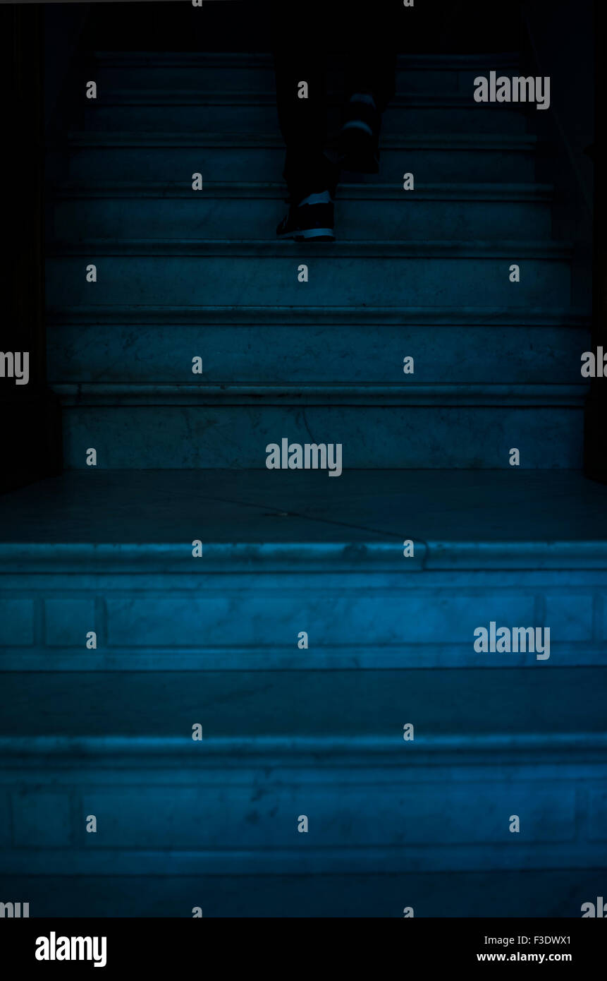 Person going up staircase, low section - Stock Image