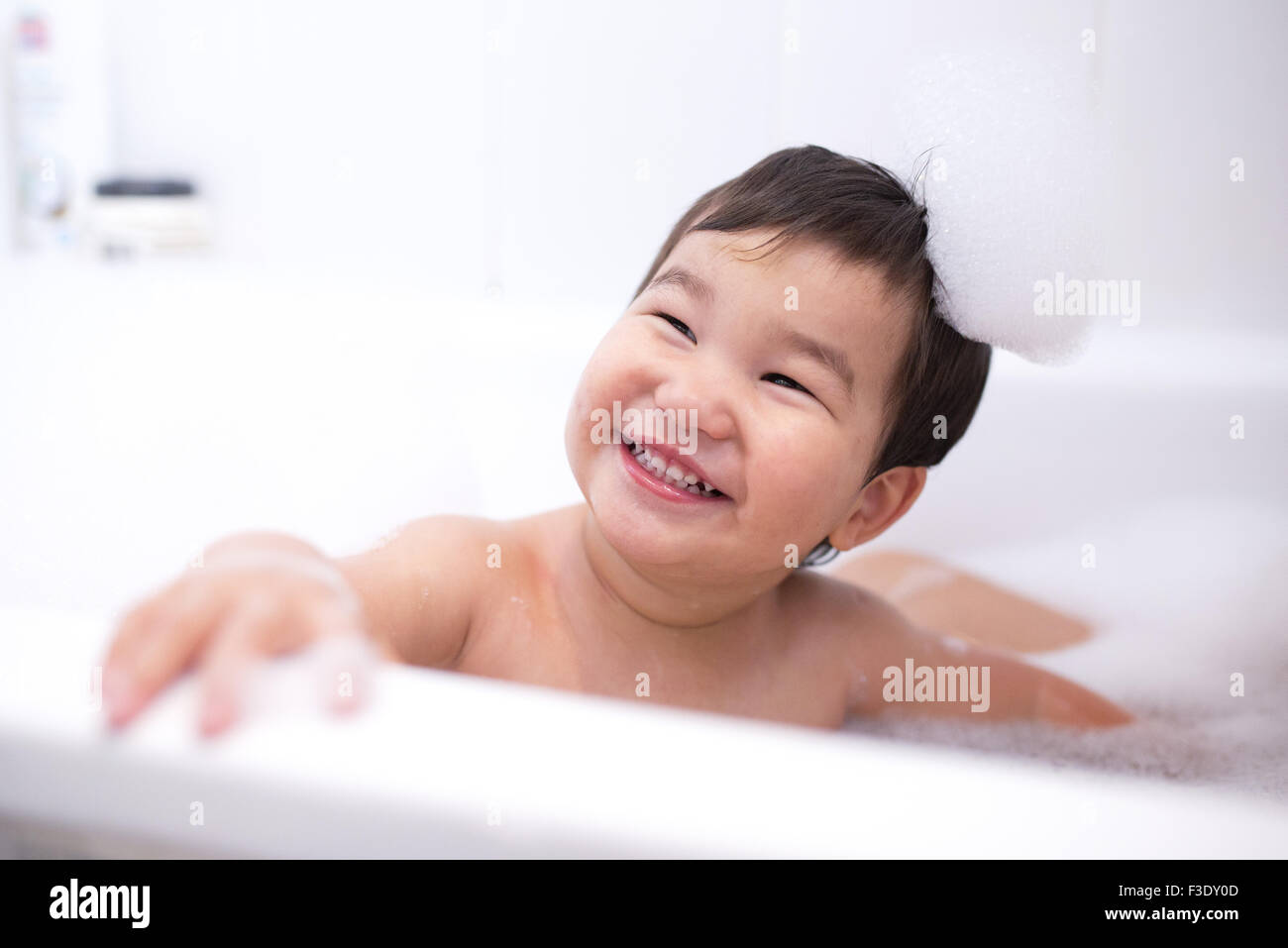 Baby boy enjoying a bubble bath, portrait - Stock Image