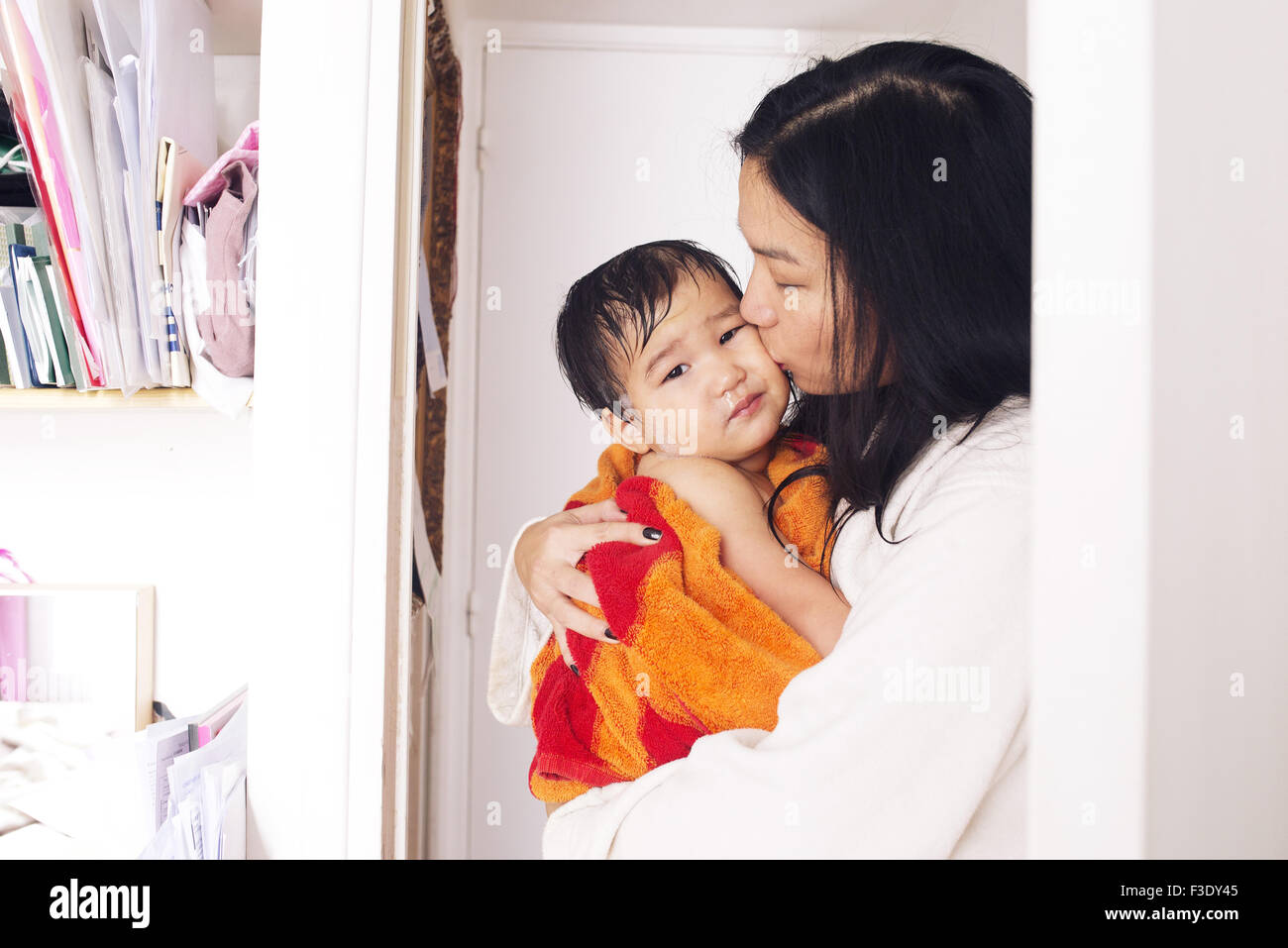 Mother comforting young son after a bath - Stock Image