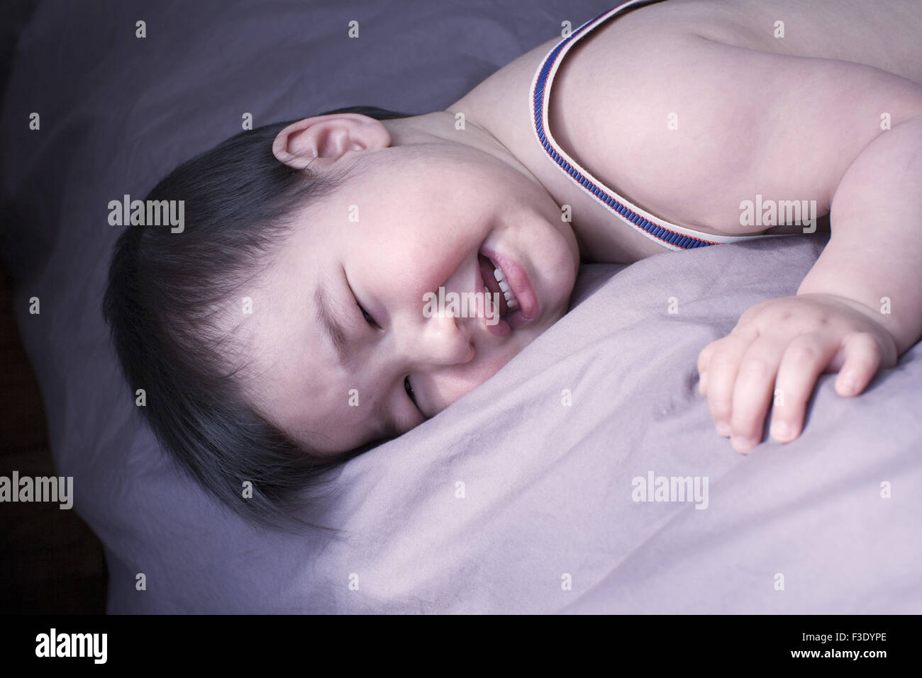 Baby boy crying on bed - Stock Image
