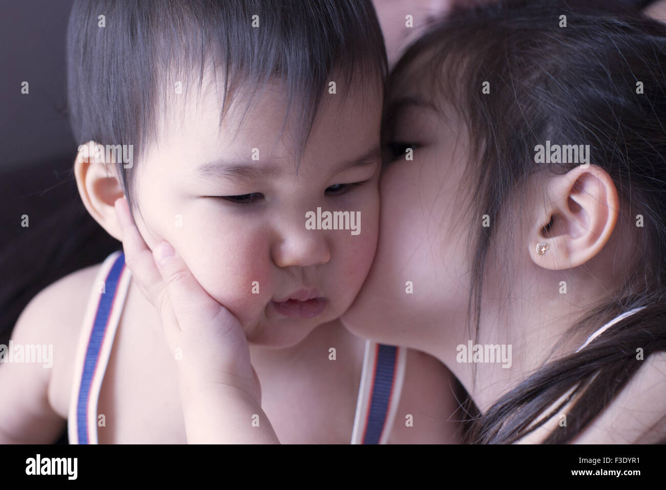Little girl kissing baby brother on cheek - Stock Image