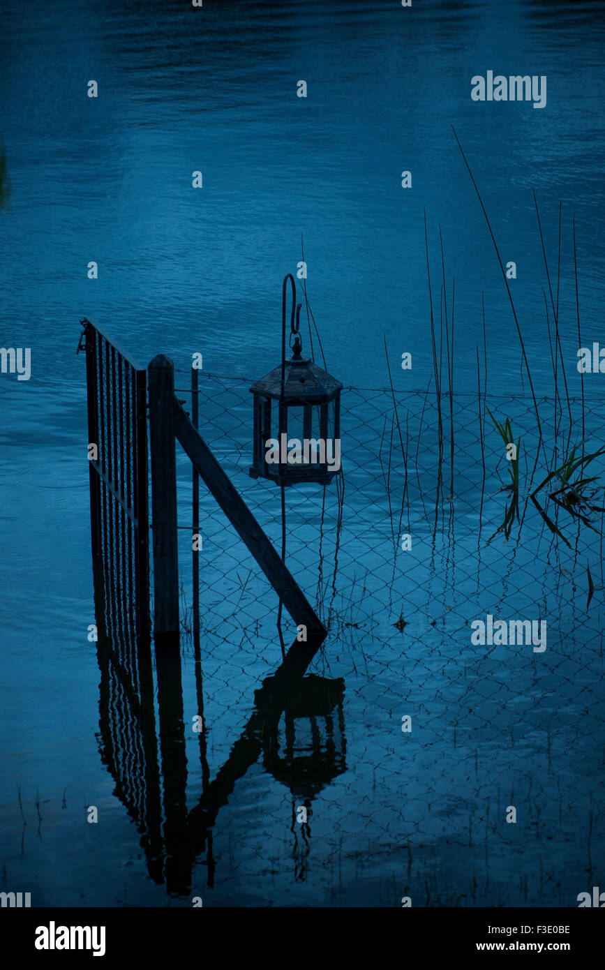 Lantern haning near gate in water - Stock Image