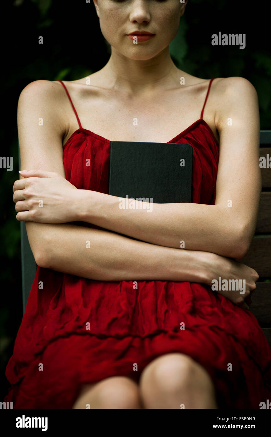 Young woman sitting with arms folded across chest, holding book protectively - Stock Image