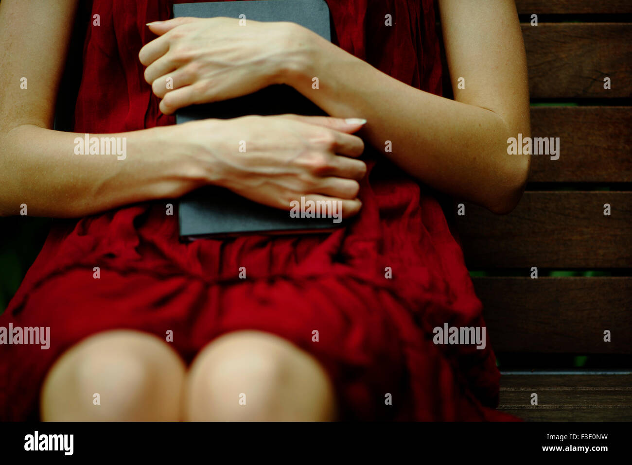 Woman sitting on bench, holding diary protectively against chest - Stock Image