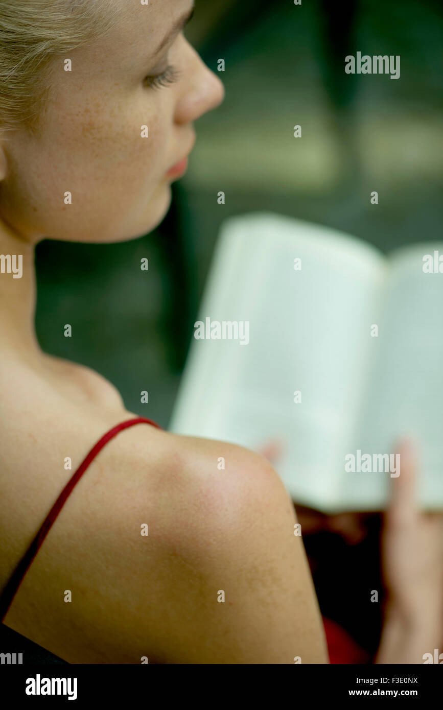 Young woman reading book, over the shoulder view - Stock Image