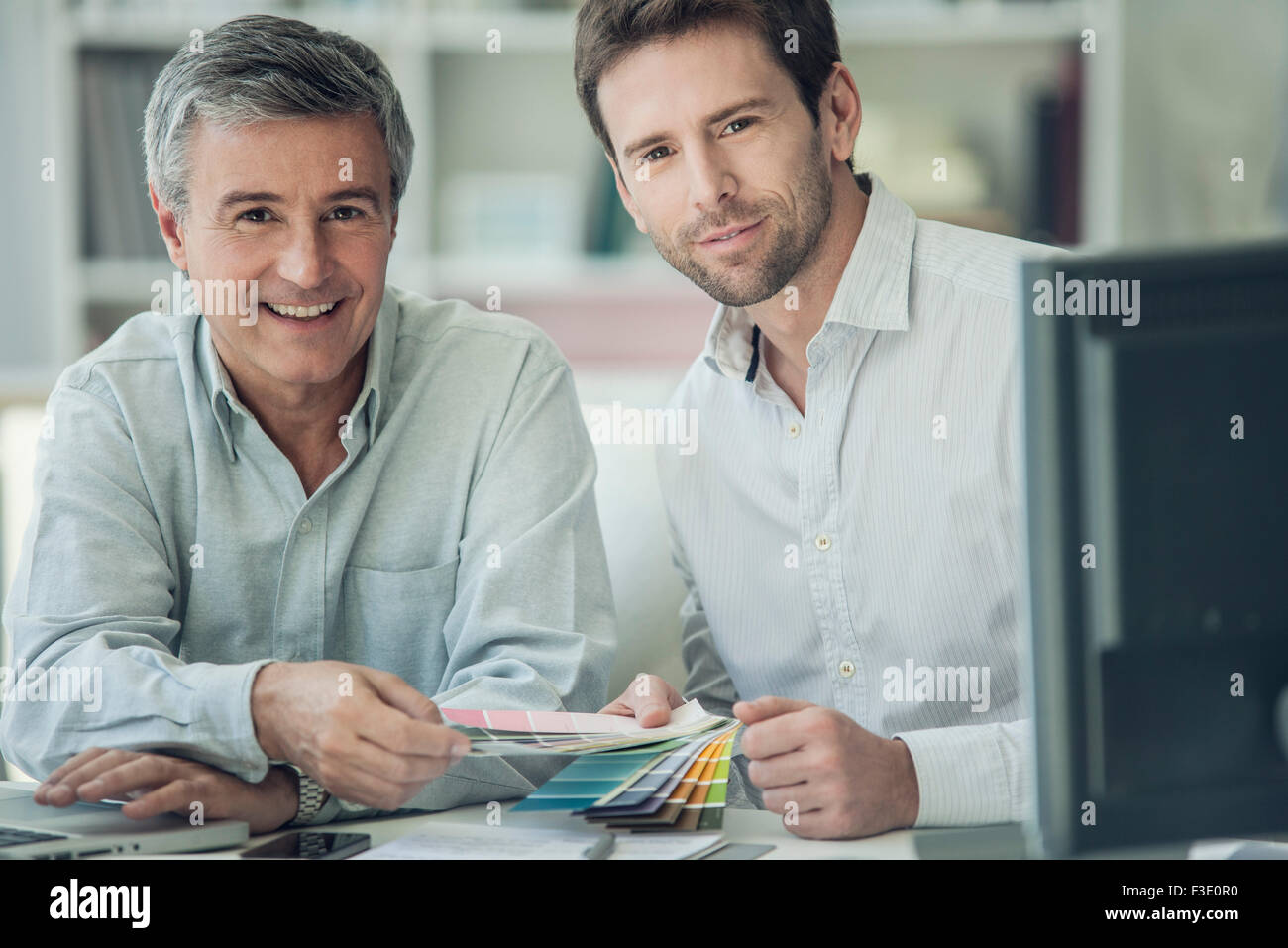 Businessmen discussing color swatches, portrait - Stock Image