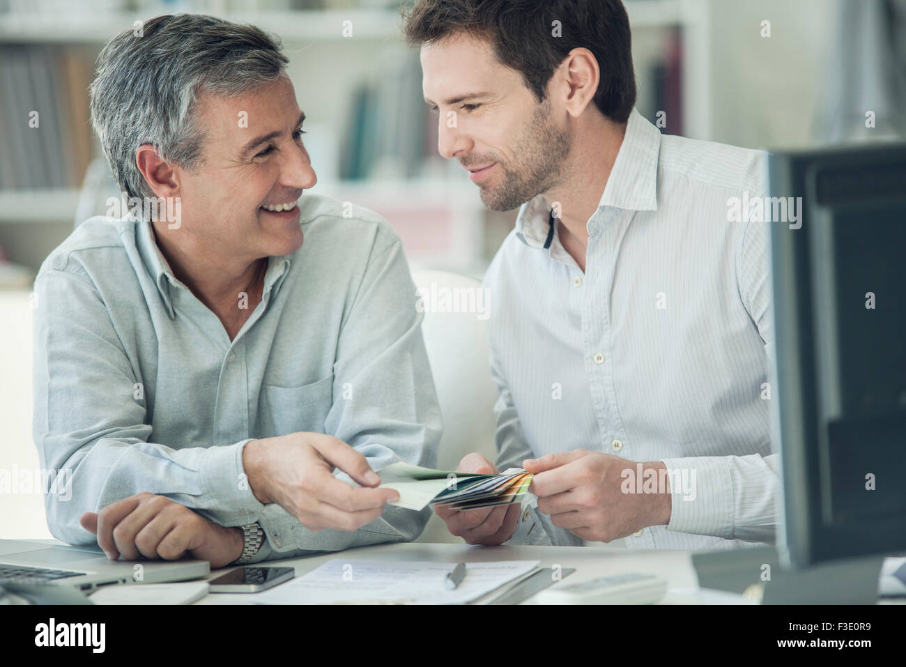 Colleagues looking at color swatches together - Stock Image