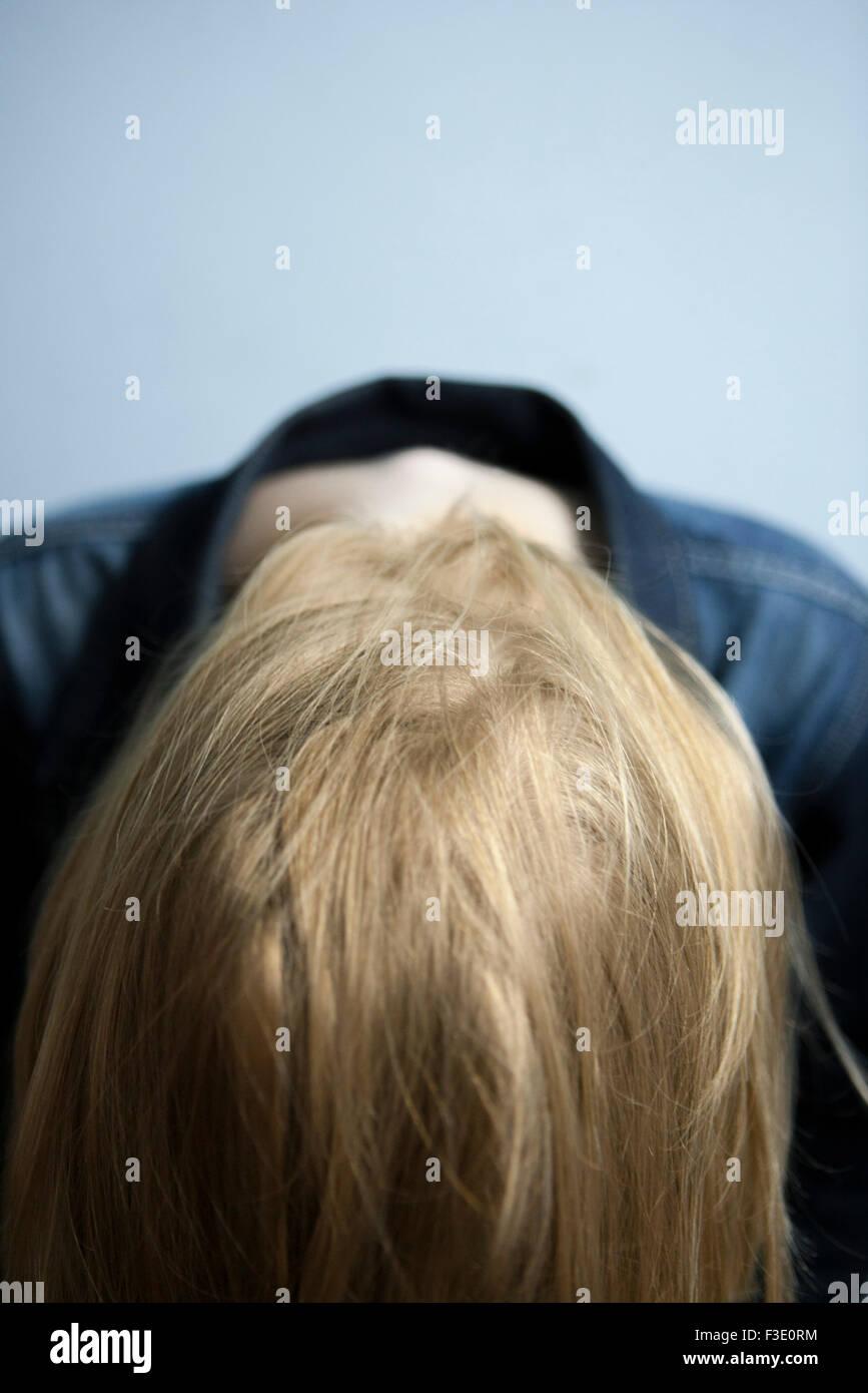 Woman leading forward letting long blonde hair hang loose - Stock Image