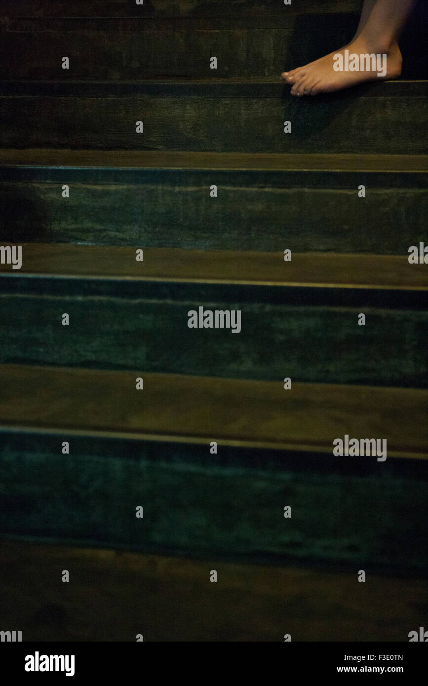 Woman's bare foot on steps of staircase - Stock Image