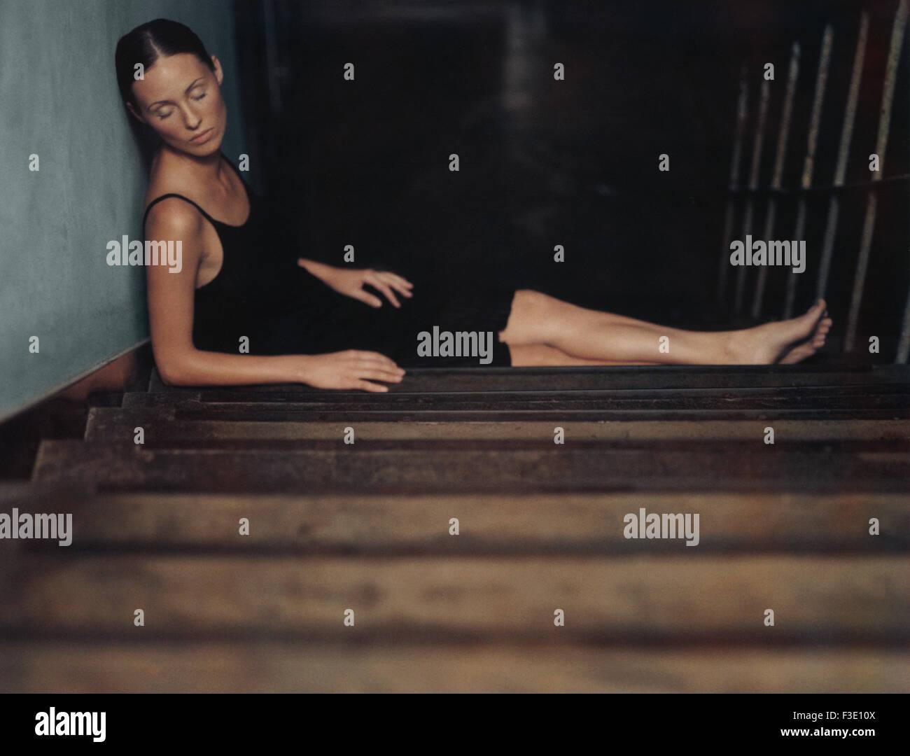 Woman sleeping on stairs - Stock Image