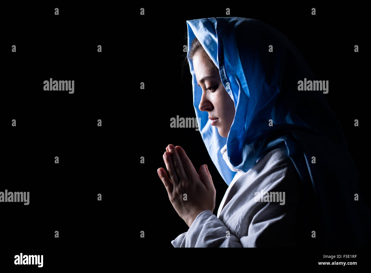 Virgin Mary with Blue Veil Praying on Black Background - Stock Image