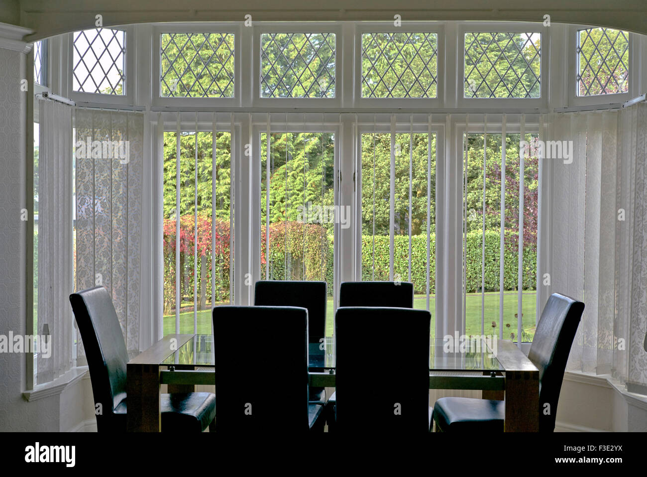 Dining room view through large leaded light bay windows of country gardens. Cumbria England UK - Stock Image