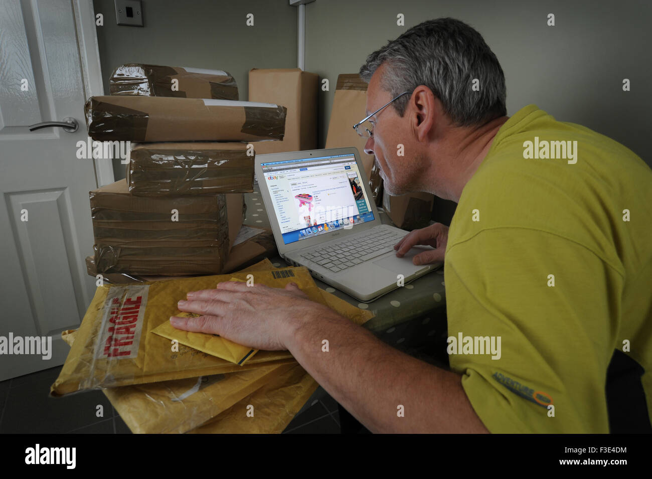 MAN AT HOME WITH PARCELS SELLING ITEMS ONLINE RE EBAY HOBBY SELLERS SELLING INTERNET INCOME TAX HMRC DECLARING INLAND - Stock Image
