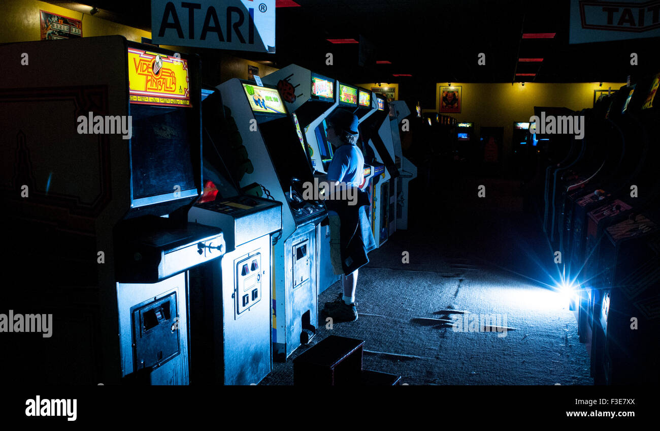 A boy plays video games in the American Classic Arcade Museum in Laconia, New Hampshire, USA. - Stock Image