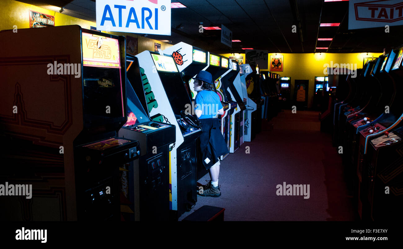 A boy plays video games inside the American Classic Arcade Museum in Laconia, New Hampshire, USA. - Stock Image