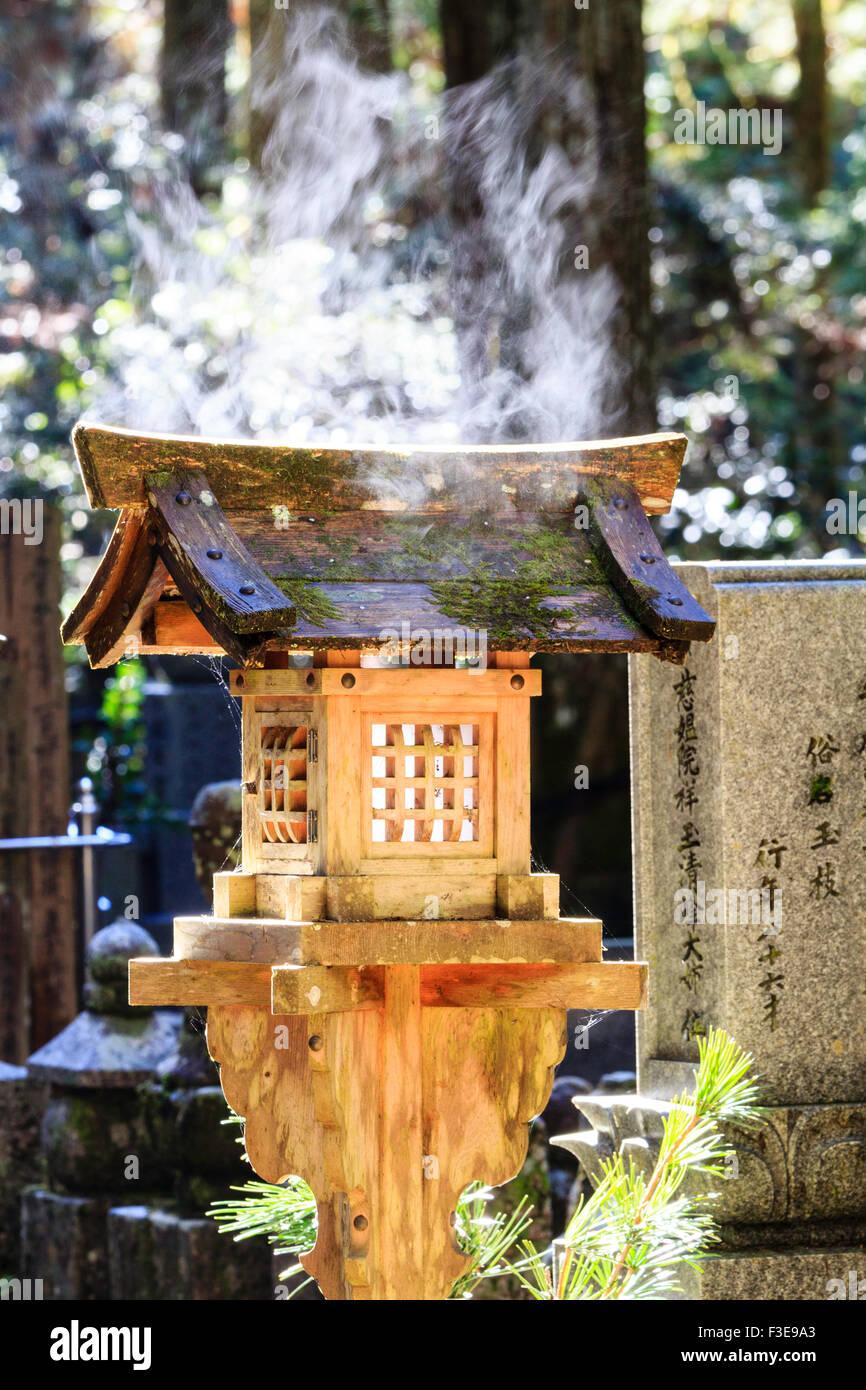 Japan, Mount Koya, Koyasan graveyard, Okunoin, wooden lantern with stream rising from wet roof - Stock Image