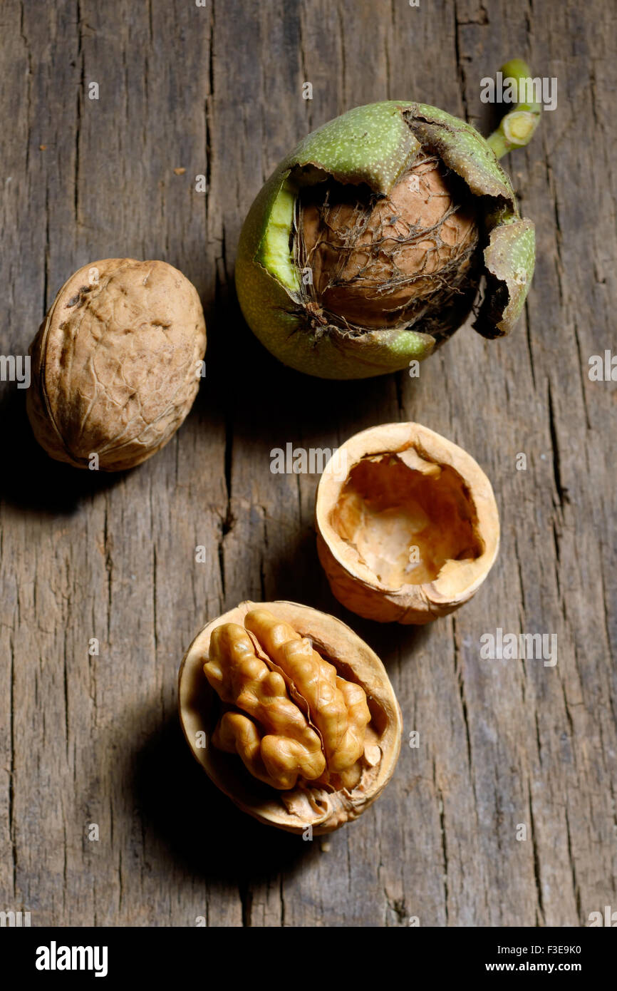 Walnuts on rustic old wooden table - Stock Image